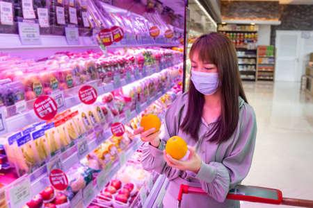 Women wear masks to shop orange fruit in supermarkets, new normal lifestyles Banque d'images