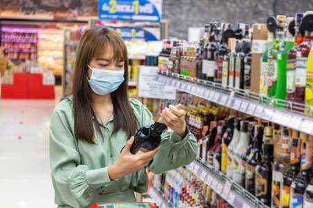 Women wear masks to shop wine in supermarkets, new normal lifestyles