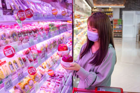 Women wear masks to shop apple fruit in supermarkets, new normal lifestyles