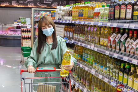 Women wear masks to shop cooking oil in supermarkets, new normal lifestyles