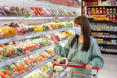 Women wear masks to shop vegetable bell pepper in supermarkets, new normal lifestyles
