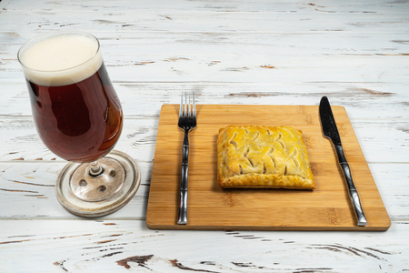 A glass, pint of beer or ale on a white rusty table with a corned beef bake.