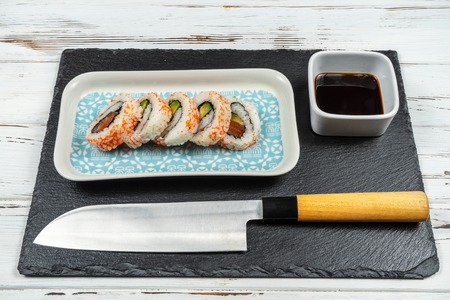 Group of fresh sushi with wooden chopsticks isolated on a white rusty background.