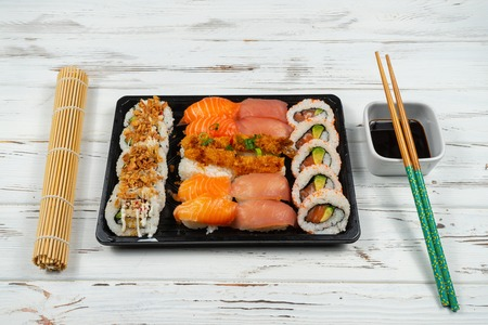 Group of fresh sushi near a bamboo mat with wooden chopsticks isolated on a white rusty background. 免版税图像