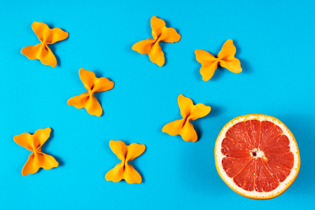 Creative summer layout made of grapefruit and colored pasta semolina papillon on bright blue background. Fruit minimal concept