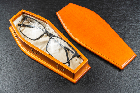 Glasses in coffin.Laser eye surgery or Buy Your Contact Lenses concept