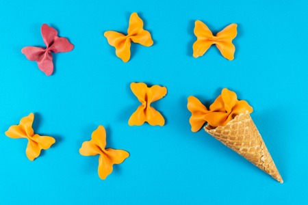 Creative summer layout made of ice cream cone, waffle cones and colored pasta semolina papillon on bright light blue background. Minimal concept.