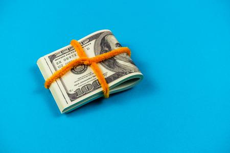 Dollar bills folded in half on light blue background. Archivio Fotografico