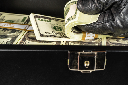 Black case full of dollar bills close up.Money bricks in case. 免版税图像