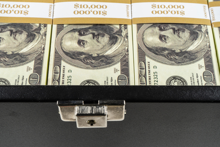 Black case full of dollar bills close up.Money bricks in case. 版權商用圖片