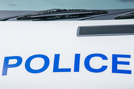 Fragment of a white police car with a word POLICE spelled out in blue in England , concept, close up. Stock Photo