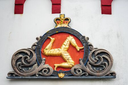 Castletown, Isle of Man, June 15, 2019. A triskelion, composed of three armoured legs with golden spurs, upon a red background. The national symbol of the Isle of Man is the Three Legs.