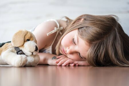 Portrait of beautiful little girl sleeping with her favorite plush stuffed animal dog doll toy Reklamní fotografie