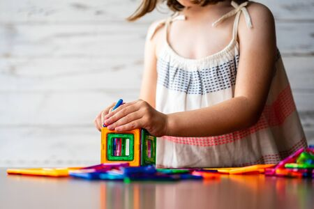 Portrait of beautiful thoughtful little girl playing colorful magnet plastic blocks kit, daydreaming and creating picture ideas in her mind. Creative process. Education and school concept