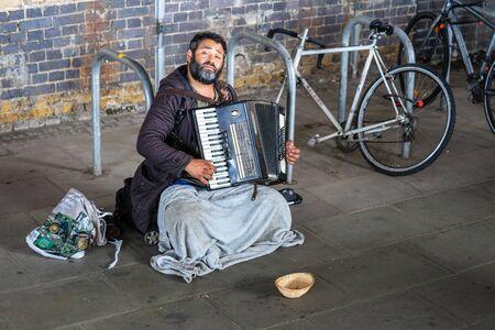 London, UK, July, 2019. Homeless Man Playing Accordion