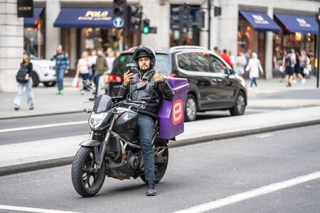 London, UK, July 28, 2019. Pizza delivery man on a motorcycle in the street using a smart phone