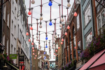 London, UK, July 28, 2019. A decorative display of large light bulbs dangling above the intersection of Ganton Street and Carnaby Street in Soho