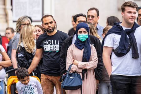 London, UK, July 28, 2019. People Watching Street Performance. Young Asian woman wearing pollution face mask