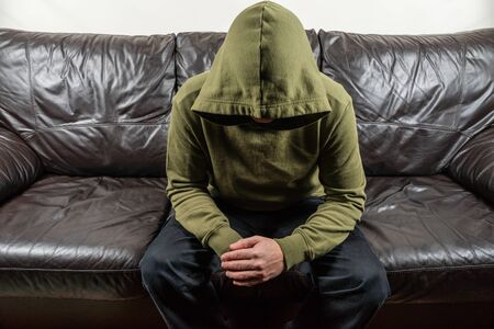 Man in dark green hoodie with unrecognizable face sitting on broun leather sofa