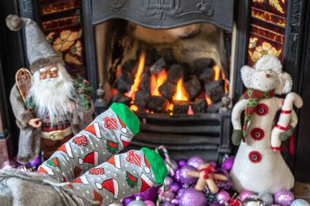 Feet in Christmas socks by the fireplace. Woman relaxes by warm fire and warming up her feet in funny socks. Close up on feet. Winter and Christmas holidays concept