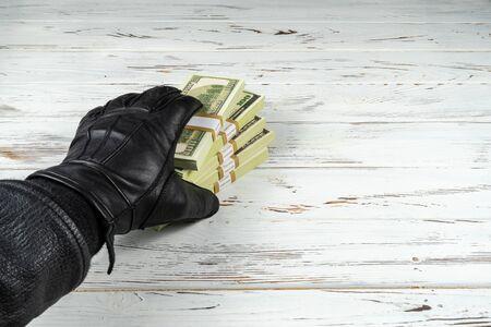 Crime Concept Man In Black Leather Gloves Holding Bricks Of Money Standard-Bild