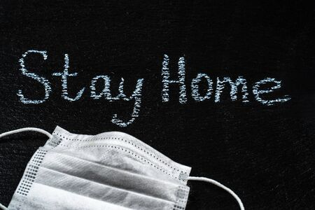 Words Stay Home on Slate Black Board. Coronavirus lockdown and stay at home concept Foto de archivo