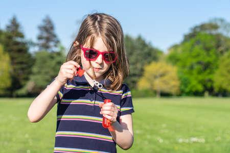 Little girl in sunglasses in summer inflates soap bubbles Banco de Imagens