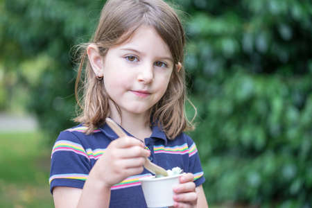 A cute little girl enjoys ice cream in park