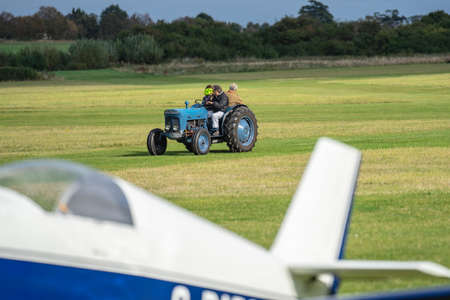 Tractor driving along the airfield runway to pick up the glider. OLD WARDEN, BEDFORDSHIRE, UK ,OCTOBER 6, 2019 Editorial