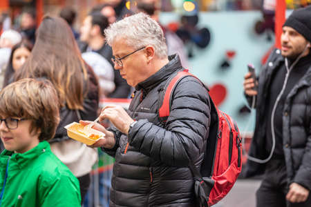 A man eats street Chinese food in China Town London. London, January 26, 2020 新闻类图片