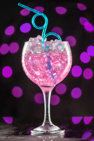 A glass with a pink cocktail filled with ice on pink lights background in a nightclub. Selective focus