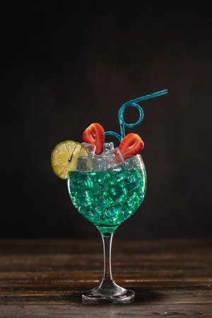 An emerald colored cocktail in an ice glass decorated with lime and strawberries with a curly drinking straw 免版税图像