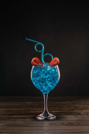 A blue colored cocktail in an ice glass decorated with lime and strawberries with a curly drinking straw