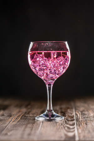 A glass with a pink cocktail filled with ice on dark background 免版税图像