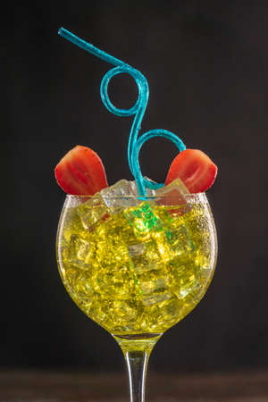 Yellow cocktail in an ice filled glass decorated with strawberries with blue Curly Party Flexible Plastic Straw