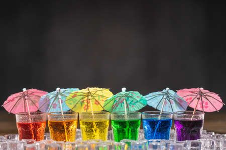 Shots with multicolored alcohol, standing in a row and decorated with cocktail umbrellas