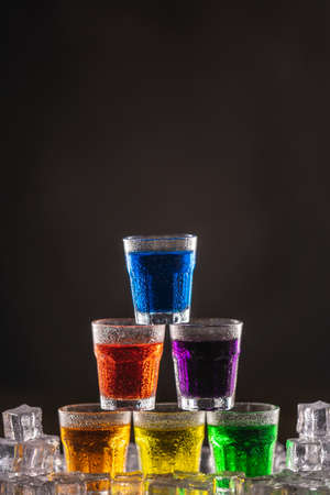 Pyramid of shots with colorful alcohol on ice