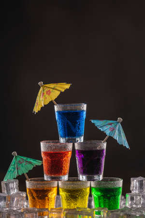 Pyramid of shots with colorful alcohol, decorated with umbrellas for cocktails