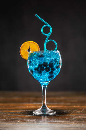 Blue cocktail with blueberry, orange slice and ice in a glass on wooden table