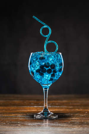 Blue cocktail with blueberry and ice in a glass on wooden table 免版税图像