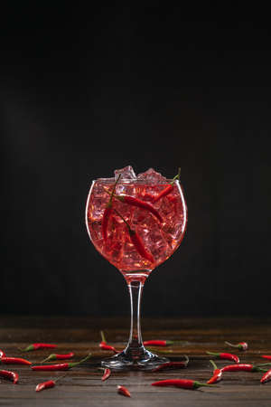 Red cocktail in a glass with ice and chili peppers. Valentines Day Concept