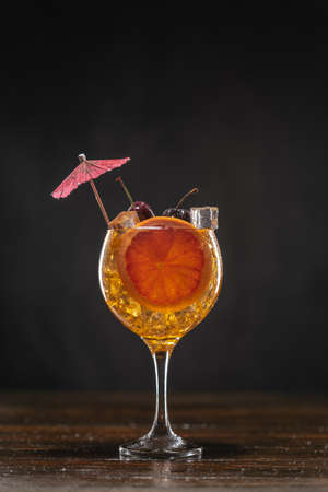 Yellow cocktail with cherry in a glass standing on a wooden table, decorated with a slice of grapefruit 免版税图像