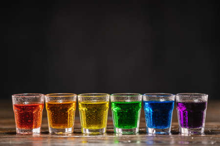 Shots with multicolored alcohol, standing in a row