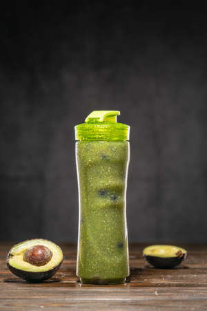 Creamy Avocado Banana Green Smoothie with Blueberry in Clear Smoothie Bottle