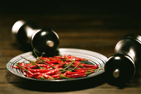 Fresh Red Birds Eye Chilli in a plate on a wooden table with a BLACK SALT and PEPPER GRINDER SET 免版税图像