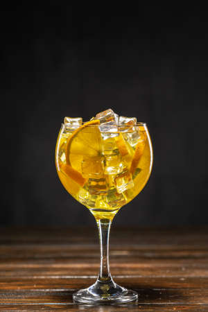 Yellow cocktail with ice and orange slices