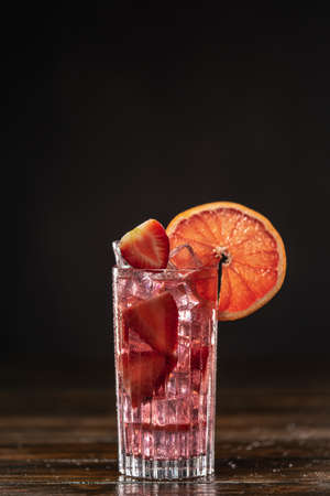 Pink cocktail with ice and strawberries, decorated with grapefruit slice