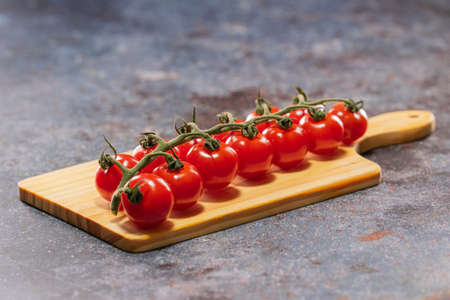 High in flavour, beautiful in colour and small in size the British Piccolo Tomatoes lying on the cutting board
