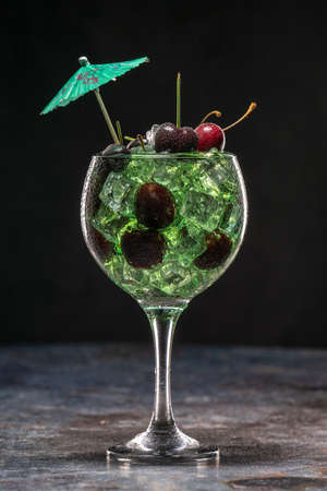 Green cocktail with ice and cherries in a glass decorated with umbrellas
