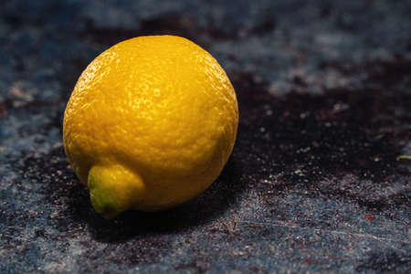 Large yellow bright lemon lying lonely on the table